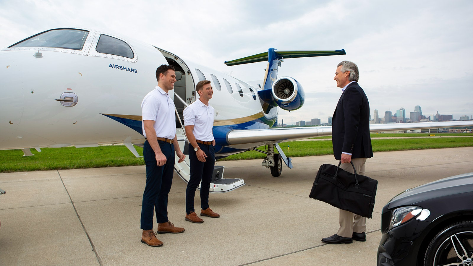 Two Airshare pilots greeting a customer as he enters the aircraft